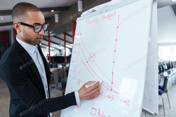 Businessman writing something on the flipchart