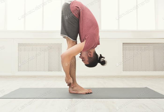 Sporty man doing Standing Forward Bend