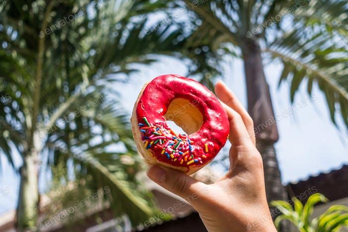 Halten Donut in der Nähe von Palmen