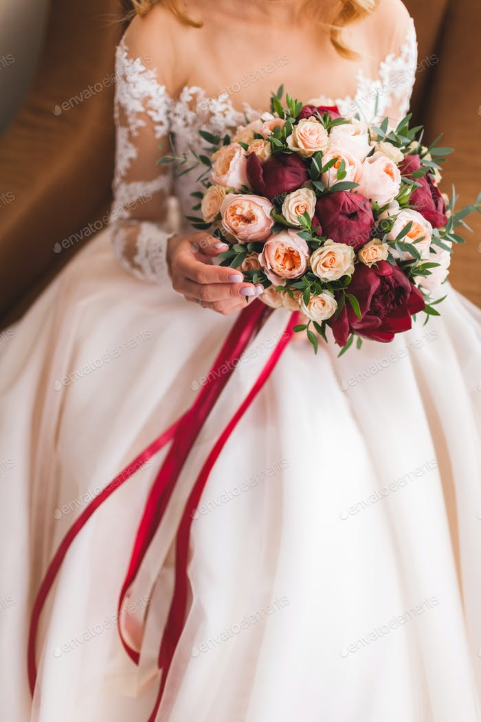 Bride holding in hands beautiful bouquet of flowers in classic style with roses, peony