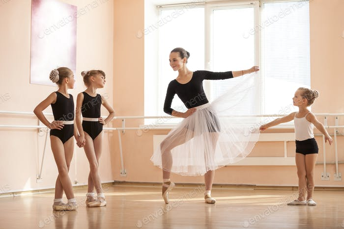 oung girl warming up and talking to younger classmates at ballet dancing class