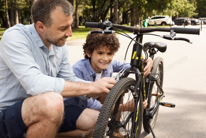 Closeup portrait of cheerful dad and son fixing bike