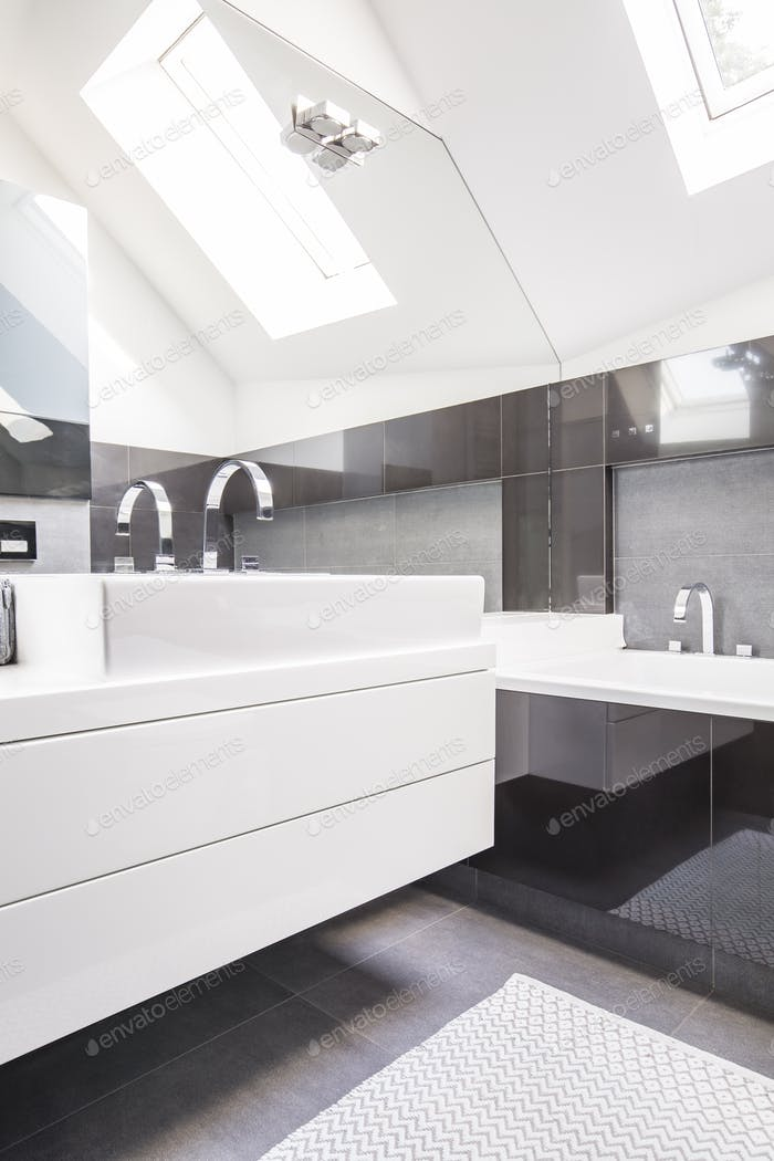 Big mirror by a modern, white washbasin cabinet in a fancy bathr