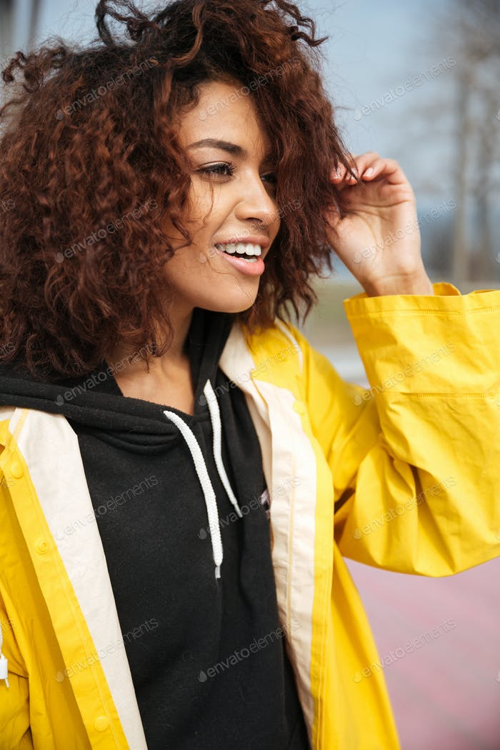 Happy african curly young woman wearing yellow coat