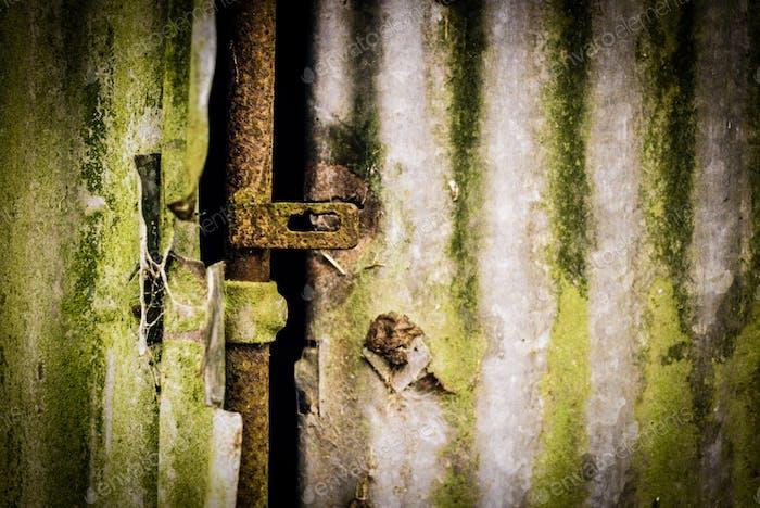 Rostige Schlossstange auf grünem Wellblech
