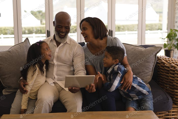 Happy multi-generation African American family using digital tablet in living room at home