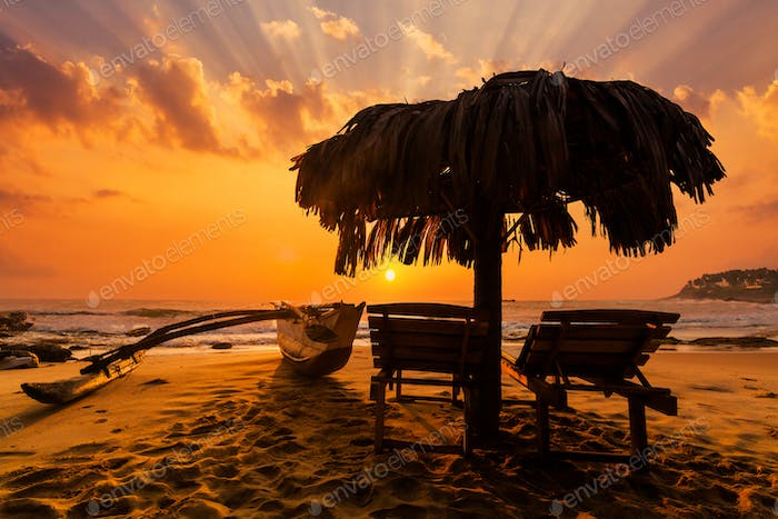 Beach loungers and umbrella at sunset on a tropical sea beach