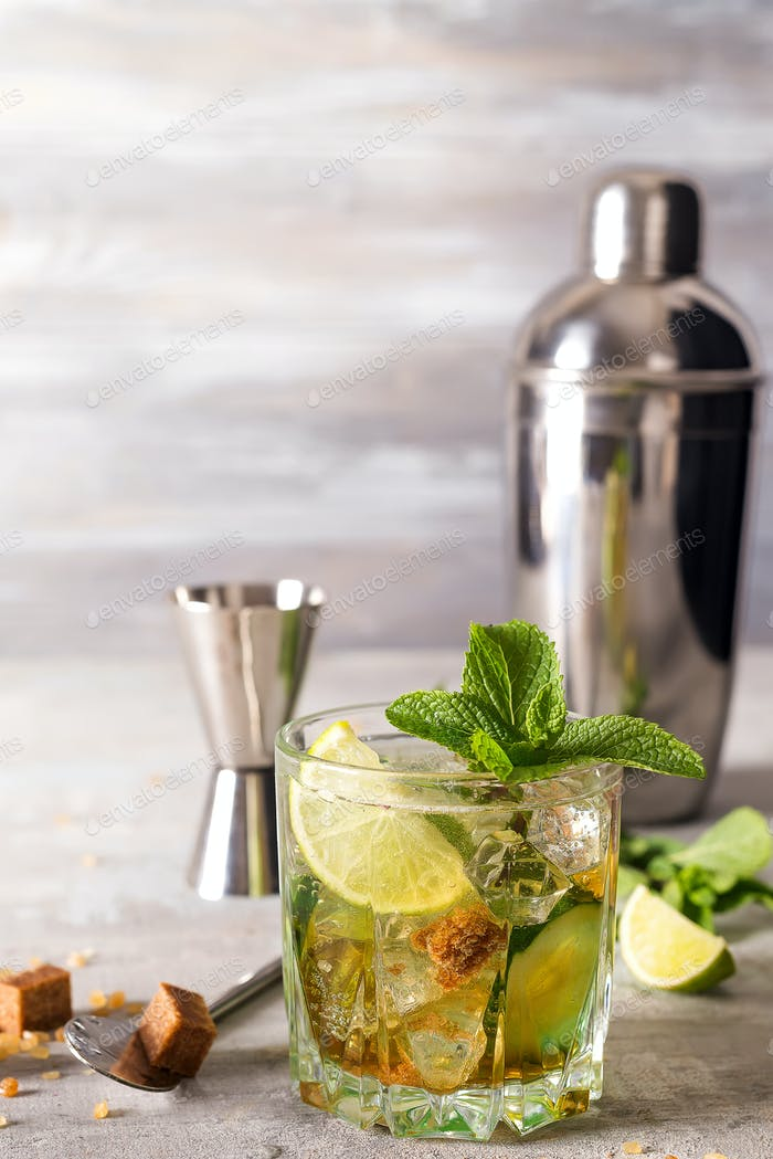 Mojito or Caipirinha cocktail. Brown sugar and an empty glass on stone