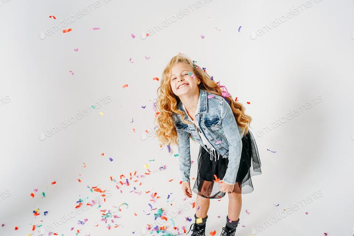 Curly hair tween girl in denim jacket and black tutu skirt and rough boots on white background