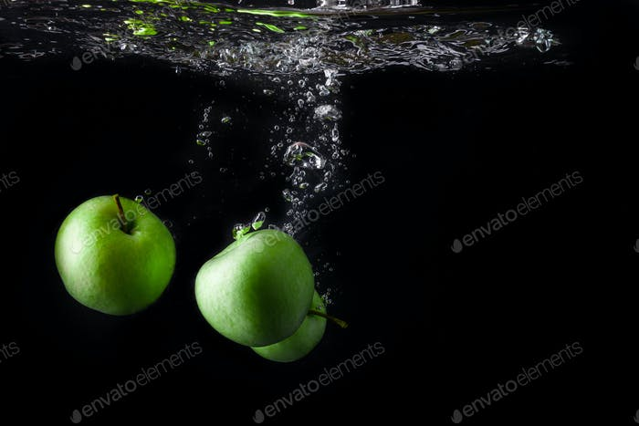 Three green apples splashing into water on black background. Copy space.