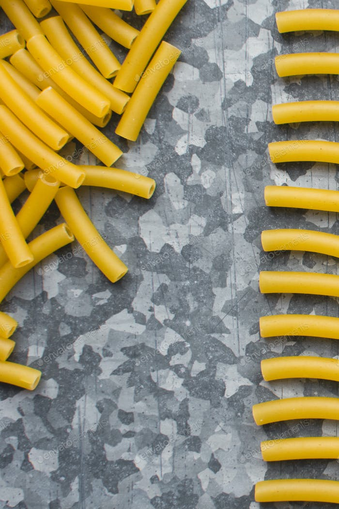 Playing with raw pasta macaroni on a metallic background