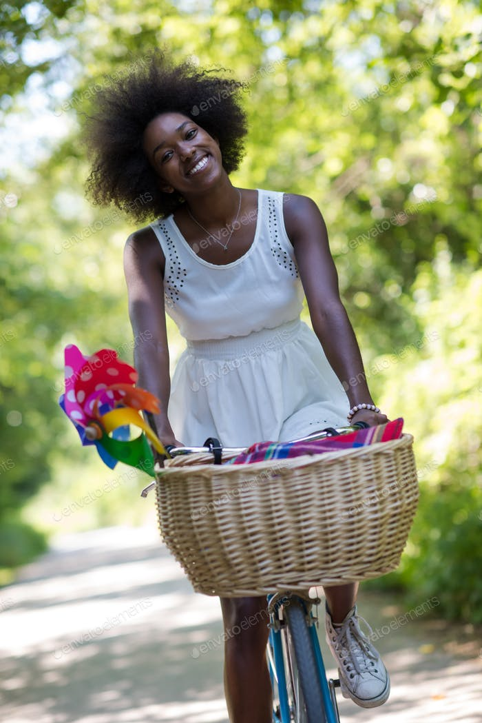 pretty young african american woman riding a bike in forest