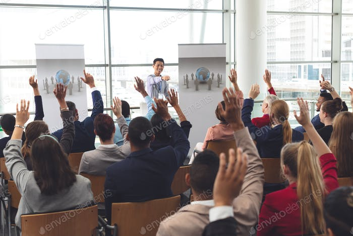 Diverse business people raising hands at business seminar in office building