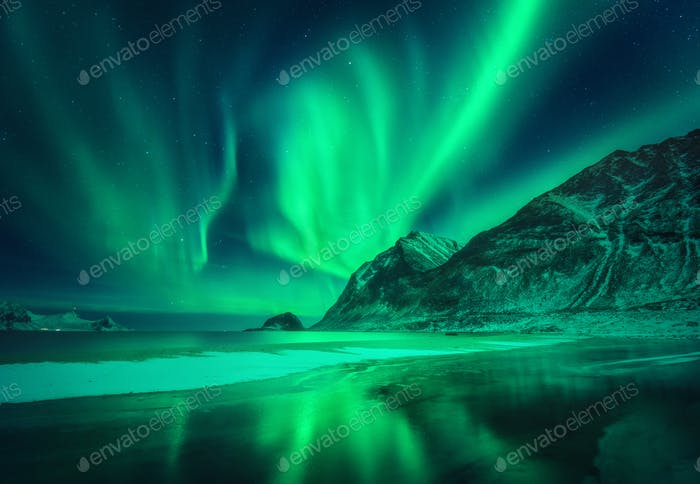 Green aurora borealis above the mountain and frosty seashore