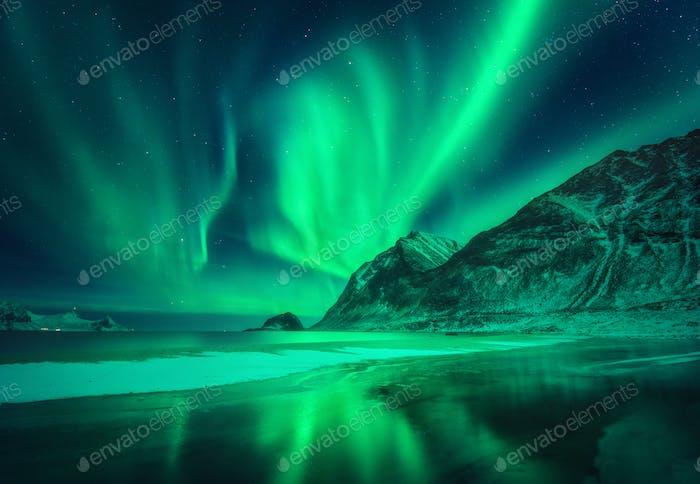 Grüne Aurora borealis über dem Berg und frostiger Küste