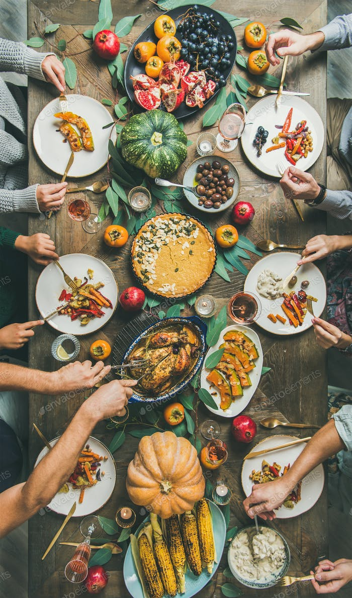 Friends feasting at Thanksgiving Day table with turkey, vertical composition