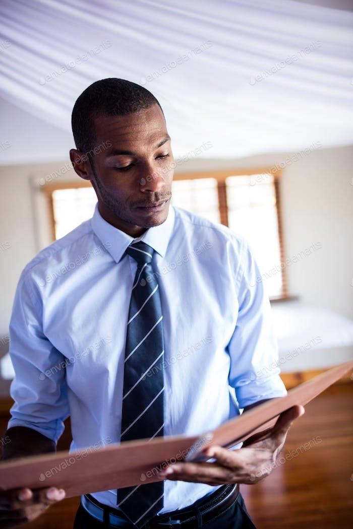 Männliche Supervisor Blick auf Datei im Hotel