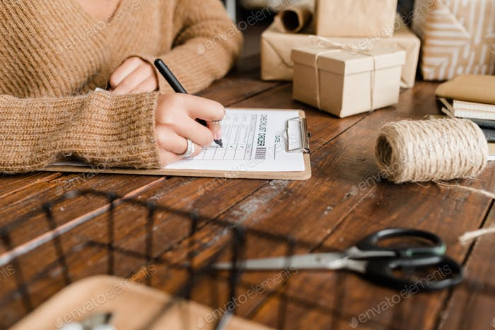 Young woman putting ticks by ordered goods in checklist by wooden table