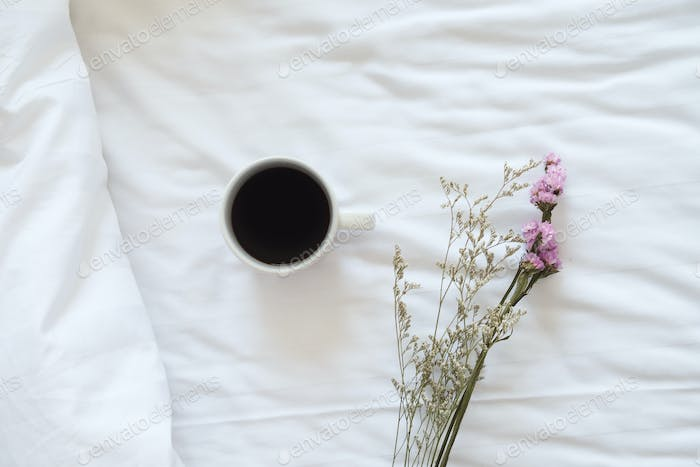 Coffee and flower in bed.