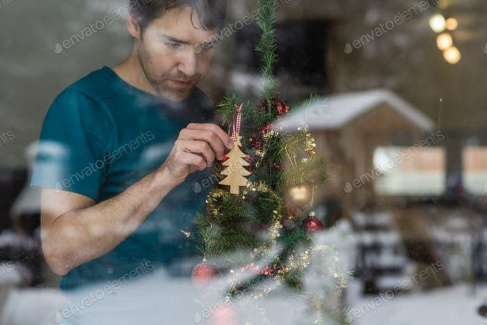 Young man hanging wooden tree on a Christmas tree