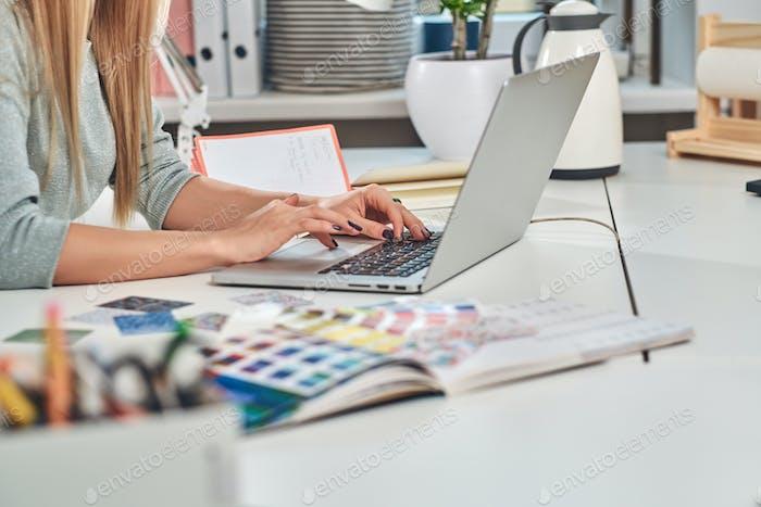 Mujer con manicura está escribiendo en la computadora portátil