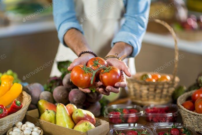 Händler, der Tomaten an der Theke anbietet