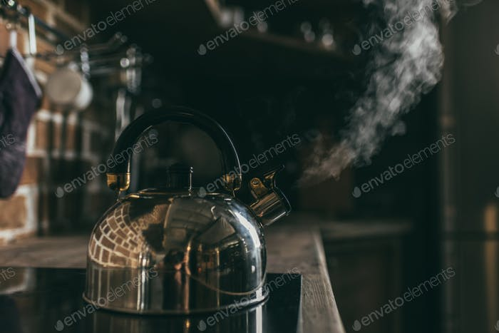 Close-up view of metallic kettle boiling on electric stove
