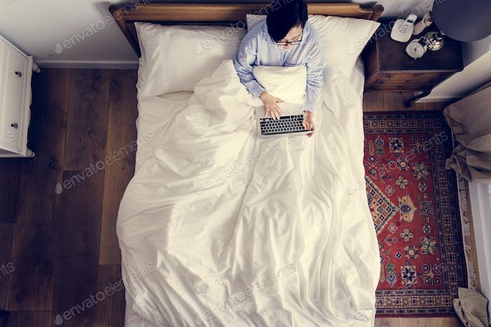 Woman in bed using a digital device