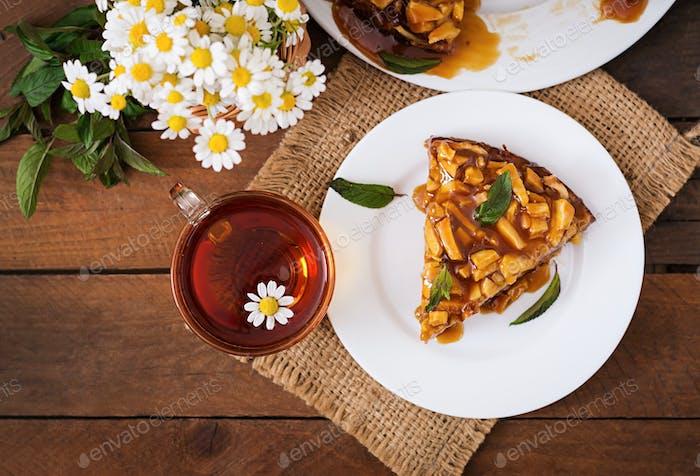 Apfelkuchen mit Karamellsauce auf einem hölzernen Hintergrund. Ansicht von oben