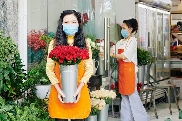 Shop owner with bucket of roses