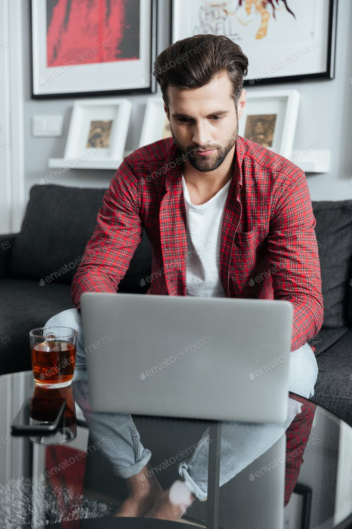 Concentrated young bearded man using laptop computer drinking tea