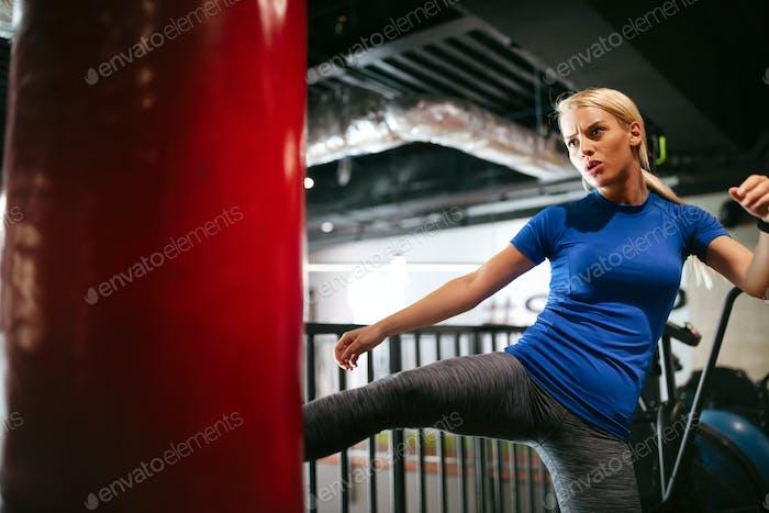 Boxtraining Frau mit Box-Trittbeutel im Fitnessstudio