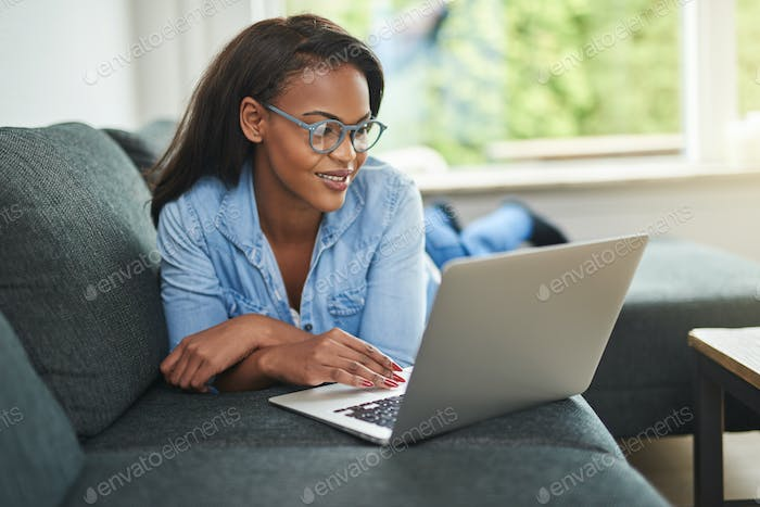 Young African woman lying on her sofa using a laptop