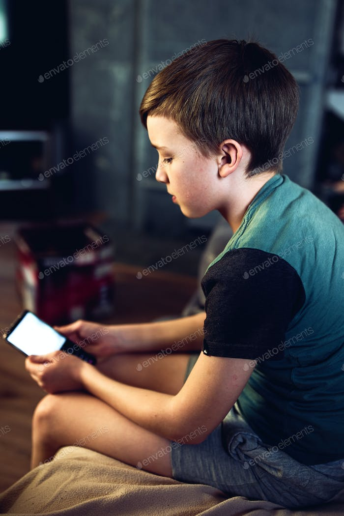 Portrait of a pensive unhappy boy with a smartphone in the room. A teenager with a mobile phone