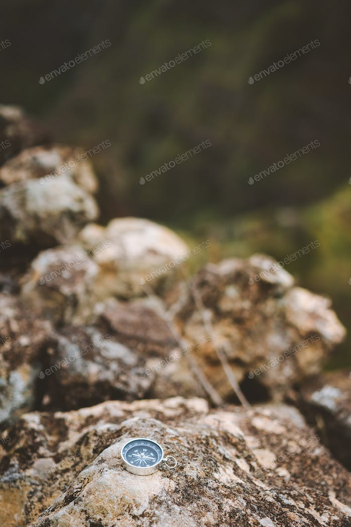 Navigation concept - Analogical compass laying on the rocky stone during trekking route in mountains