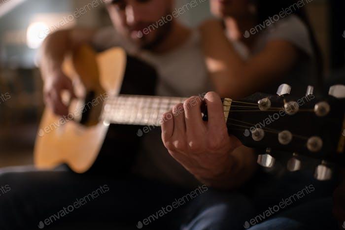Anonymer Mann spielt Gitarre in der Nähe Freundin