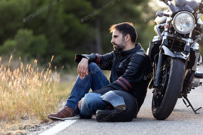 Young male leaning the motorbike.