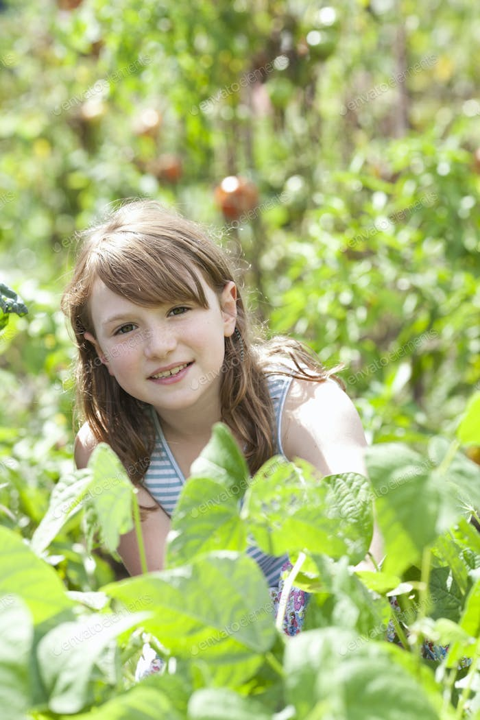 A young girl sitting among the green foliage of a vegetable garden,picking fresh produce