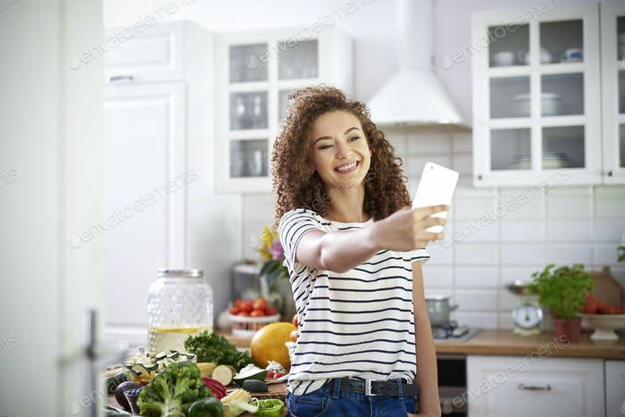 Woman taking selfie in the kitchen