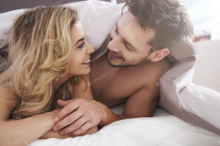 Charmantes Paar mit einer Bettdecke bedeckt