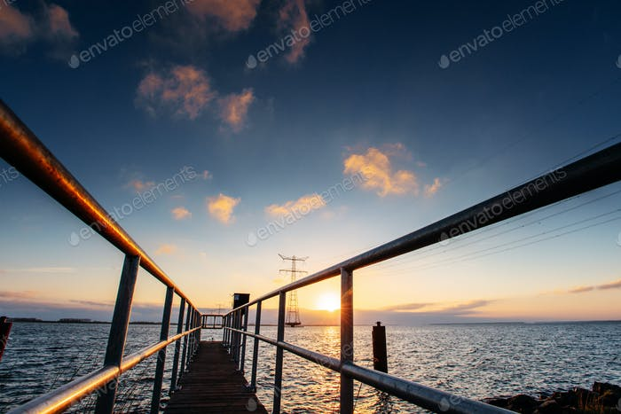 Fantastic sunset that illuminates the long pier on the lake