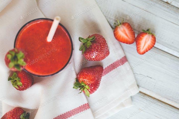 Ein Glas Erdbeer-Smoothie auf weißem Holzhintergrund