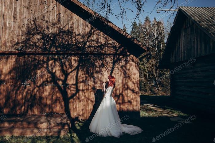 Stilvolle Braut entspannend im Sonnenlicht auf dem Hintergrund der Holzwand im Land