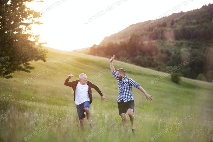 An adult hipster son and his senior father jumping in nature at sunset.