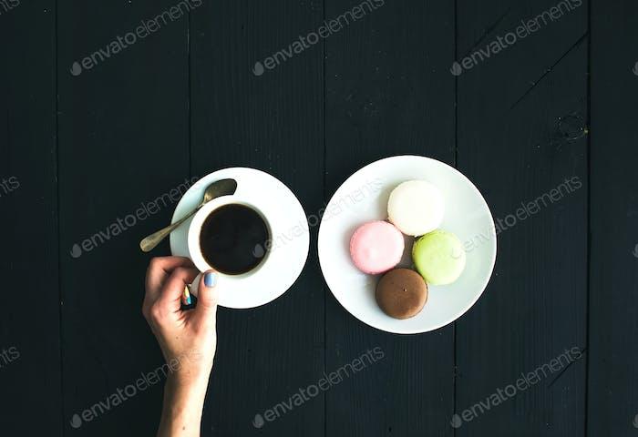 Macaron cookies, cup of espresso and ladie's hands over black wooden backdrop