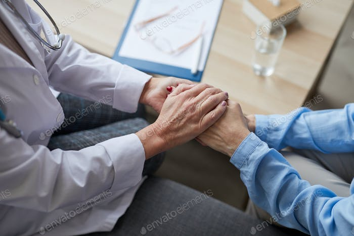 Caring Female Doctor Holding Hands with Patient Closeup