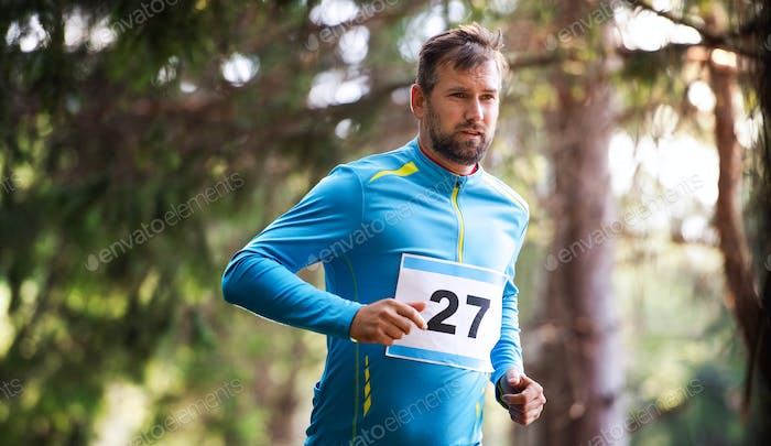 Front view of young man running a race competition in nature.