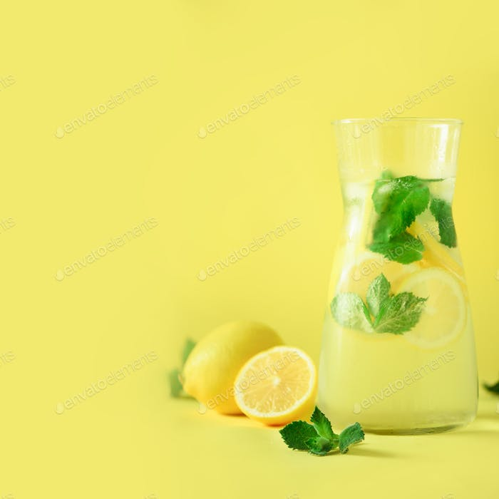Citrus lemonade - mint, lemon and tropical monstera leaves on yellow background. Square crop. Detox