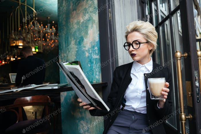 Close-up portrait of girl sitting in cafe with magazine
