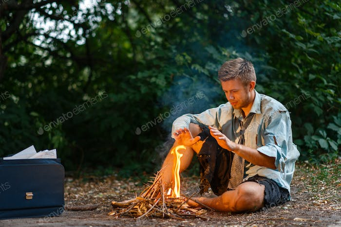 Alone businessman warms by the fire on lost island